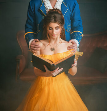 Woman princess holding a book without title cover design reads the text. Fantasy man enchanted prince hugging a beautiful lady by shoulders. Girl in yellow medieval historical dress vintage gown.