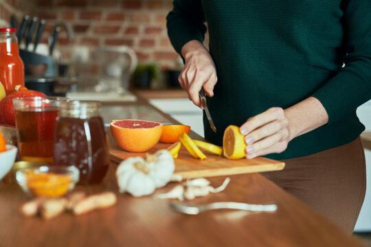 Unrecognizable woman cutting lemon for winter tea