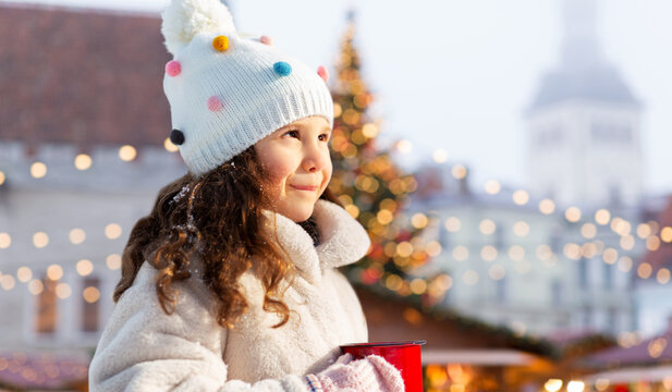 winter holidays and children concept - happy little girl with cup of hot tea over christmas market at old town hall square, tallinn, estonia