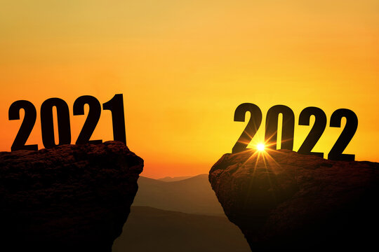 New Year's Eve 2022 on the mountain at sunset, concept. 2021 and 2022 on the cliff at sunrise, creative idea. Free space for design