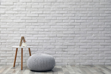 Obraz Comfortable knitted pouf, table and decor elements near white brick wall indoors, space for text. Interior design - fototapety do salonu