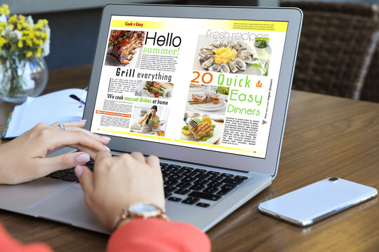 Woman reading online magazine on laptop at wooden table, closeup