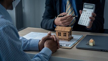 Fototapeta Sales representatives and new homeowners sign a home purchase or rental contract on the table. Real estate concepts or bank officers explain loan interest to customers with home or office loan contrac obraz