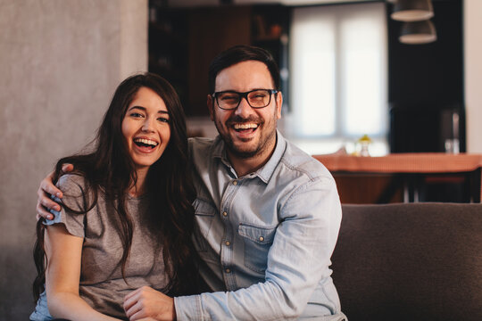 Portrait of a young happy couple sitting embraced on a sofa