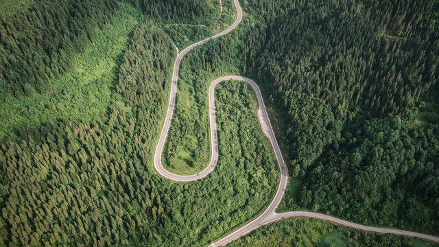 Flight over the summer mountains with mountain road serpentine, river and forest. Ukraine, Carpathian mountains. Landscape photography