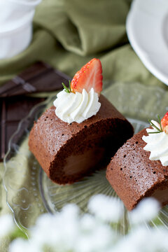 Chocolate Swiss Roll Cake with Chocolate cream filling and Strawberry set on cafe table.