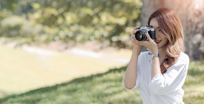 Beautiful smiley asian woman using camera outdoors under the sunlight.