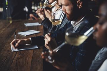 Fototapeta Caucasian man and african woman sommelier bartender smelling white wine and making degustation card obraz