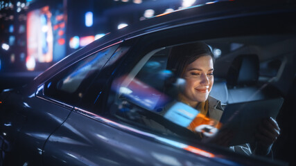 Obraz Stylish Female is Commuting Home in a Backseat of a Taxi at Night. Beautiful Woman Passenger Using Tablet Computer while in Car in Urban City Street with Working Neon Signs. - fototapety do salonu