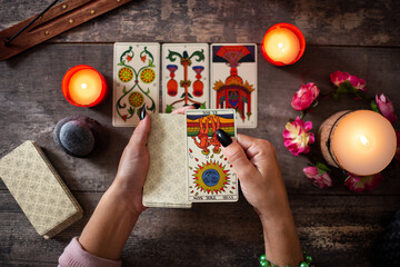 Fototapeta Fortune teller reading a future by tarot cards on rustic table obraz