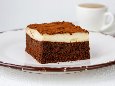 Piece of moist chocolate sponge cake with custurd cream in white plate on table.It called Islak kek or Aglayan Kek in Turkish. Homemade brownie cake with cocoa. Bakery, pastry for tea time in Turkey