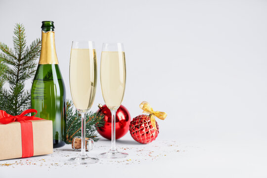 Happy New Year! Bottle of sparkling wine, glasses and festive decor on white background, space for text