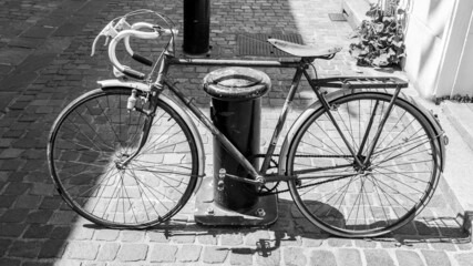 Grayscale shot of an old french style rusty bike in France