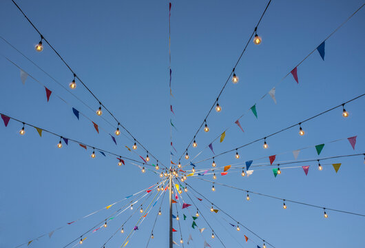 Garland with colorful pennants and light bulbs on pole over blue sky