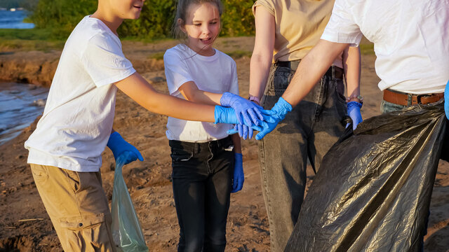 group of four people with a teenager collect garbage on the shore. Joint work. Environmental education concept.