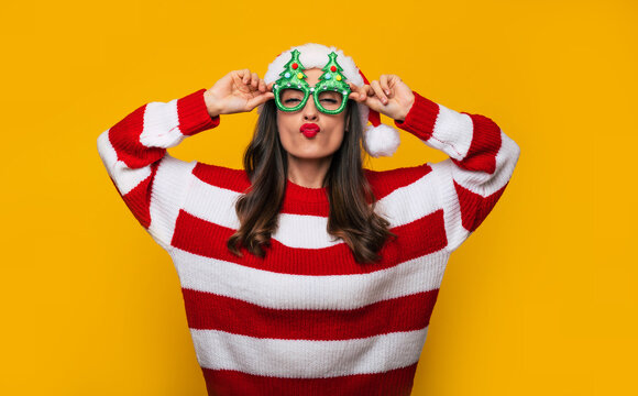 Crazy and excited beautiful modern woman in funny Christmas glasses and Santa hat is having fun while posing against a yellow wall