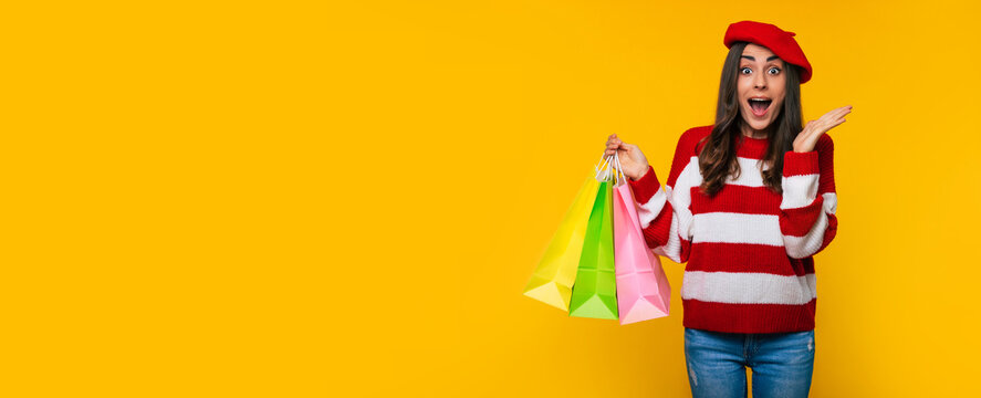 Banner photo of a gorgeous stylish woman in a striped sweater and red beret with many colorful shopping bags in hands isolated on yellow background