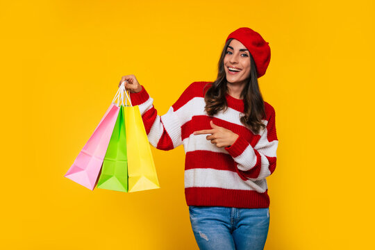 Gorgeous stylish woman in a striped sweater and red beret with many colorful shopping bags in hands is posing isolated on yellow background