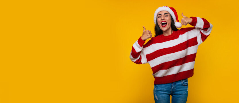 Wide length banner photo of an excited cute brunette woman in red Christmas hat while she is posing against yellow wall