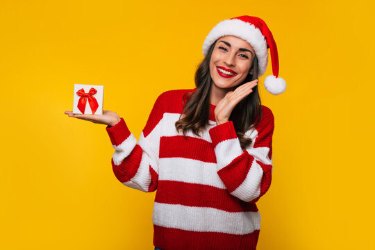 Cute excited smiling woman with Christmas gift box in hands is having fun while posing on yellow background