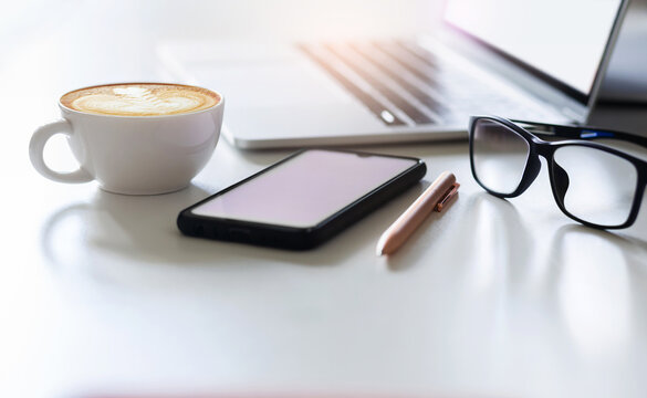 Focus on white coffee cup with latte coffee and eyeglasses, mobile, laptop on white table