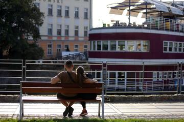 Fototapeta Para młodych ludzie wypoczywają, siedzą na ławce we Wrocławiu nad kanałem.  obraz