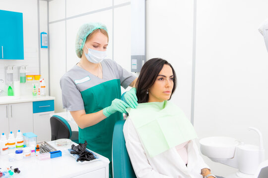 The dentist's assistant puts the protection on the patient, the napkin on the chest