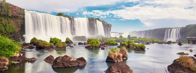 Fototapeta Iguazu waterfalls in Argentina, view from Devil's Mouth. Panoramic view of many majestic powerful water cascades with mist and clouds. Panoramic image of Iguazu valley with stones in water. obraz