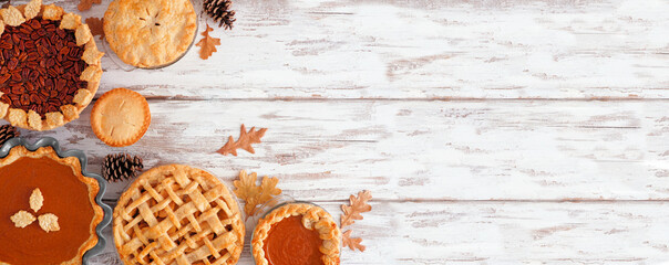 Fototapeta Selection of homemade autumn pies. Pumpkin, apple and pecan. Above view corner border on a white wood background with copy space. obraz