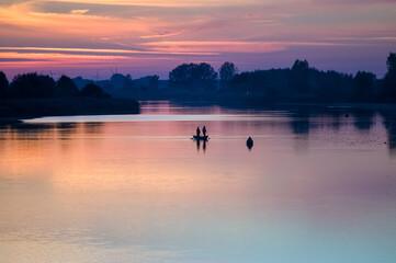 Fototapeta Łódka wędkarze na rzece w pięknym oświetleniu zachodzącego słońca  obraz