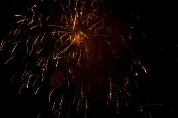 Salute in the sky. Explosion of fireworks in the night sky. Firecrackers flapping sparks in a dark space. Festive fireworks.