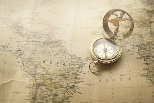 Retro style antique golden compass (sundial) and old nautical chart close-up. Vintage still life. Sailing accessories. Wanderlust, travel and navigation theme. Graphic resources, copy space