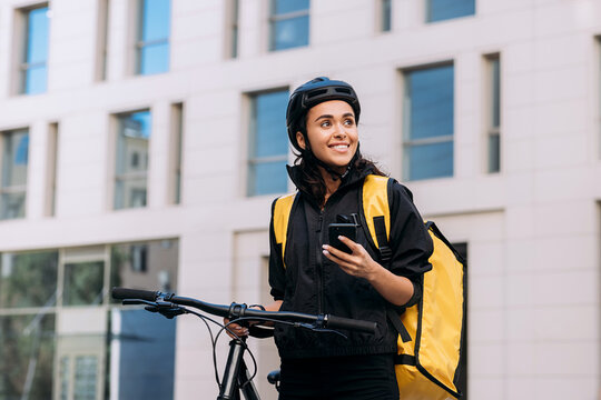 Food delivery woman using smart phone on street in city. Female courier in cycling helmet with backpack looking away.