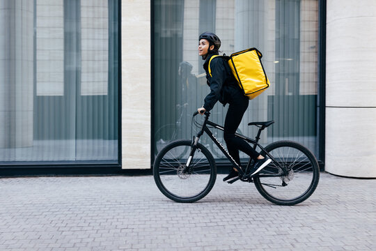 Side view of a young woman riding her bike in the city. Courier with a thermal backpack in her way to deliver food to a customer.