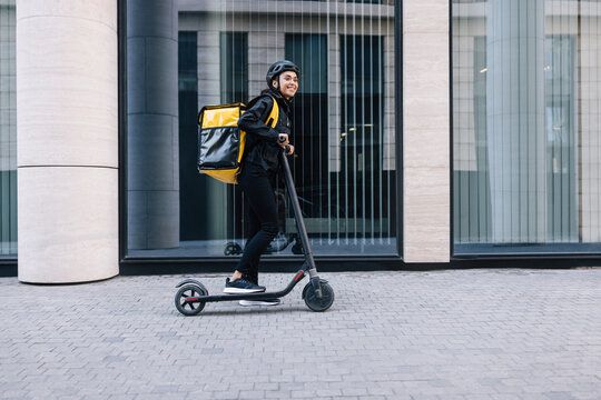 Cheerful female courier standing on electric scooter. Woman in cycling helmet wearing thermal backpack looking away.