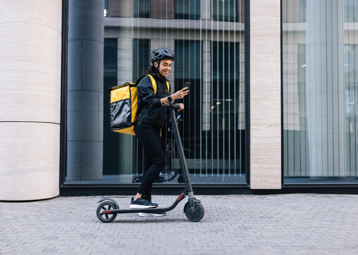Smiling female courier in uniform with thermal backpack standing on an electric scooter looking on smartphone