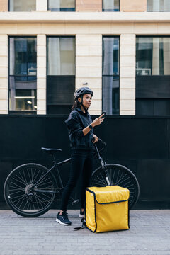 Woman courier in uniform standing in the city holding smartphone checking customer address