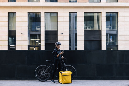 Side view of delivery woman holding a mobile phone, wearing a cycling helmet. Young female standing in the city with bicycle and thermal backpack.