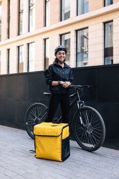 Portrait of a delivery woman standing in the city with bicycle and thermal backpack