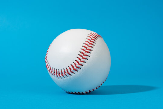 Minimalist stylish photo of baseball ball with harsh shadow. Close-up image of baseball ball on blue background in perspective.
