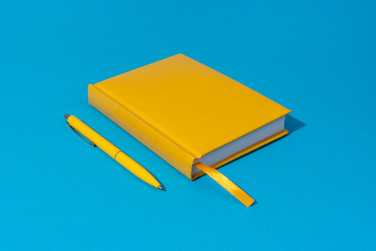 Photo of closed yellow notebook and ball-point pen over blue background. Minimalist image of closed diary and yellow pen as back to school concept.