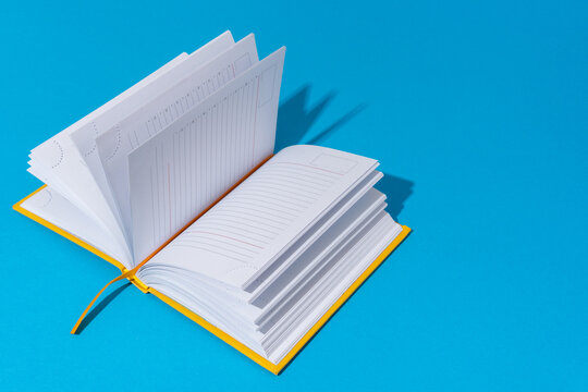 Photo of opened notebook on blue background with copy space. Minimalist image of blank diary in perspective. Stylish shot of a notebook with harsh light and shadow.