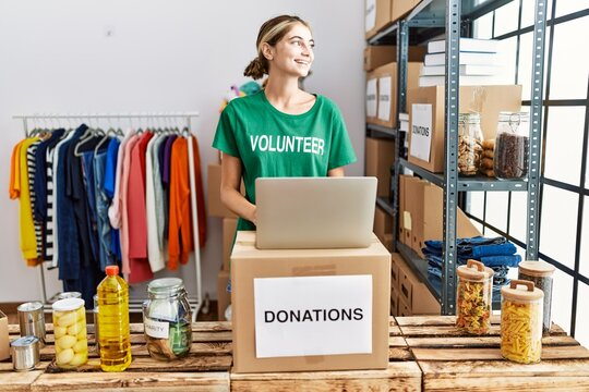 Young blonde woman wearing volunteer t shirt at donations stand looking away to side with smile on face, natural expression. laughing confident.