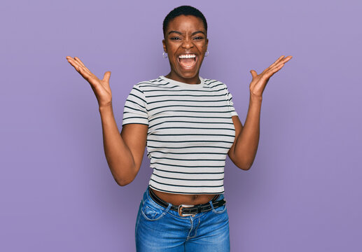 Young african american woman wearing casual clothes celebrating victory with happy smile and winner expression with raised hands