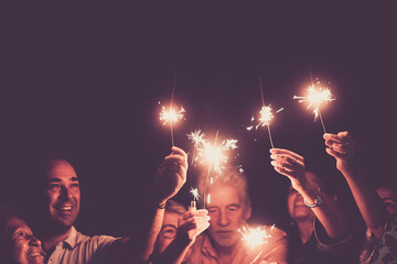 Fototapeta Family celebrating holding burning sparkles with arms raised. Group of multi generation family celebrating a birthday or anniversary or new year. Men and women having fun together obraz