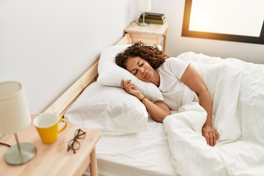 Middle age hispanic woman sleeping on the bed at bedroom
