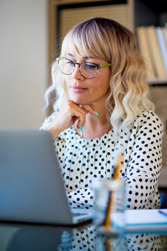 Businesswoman using laptop on desk. Confident young woman working on laptop at home office. Focused woman with eyeglasses reading using laptop at office. Executive reading work emails using laptop