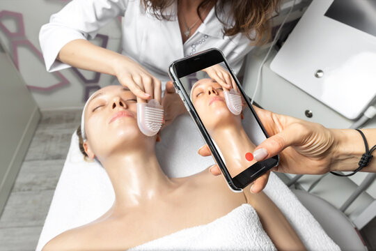 Hand holding smartphone making online live video stream of cosmetician doctor facial care procedure tutorial for online workshop master class in social media network. Remote distance learning concept