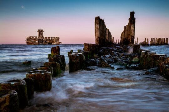 Zachód słońca krajobraz nad morzem. Drewniany falochron lina do platformy torpedowej II wojny światowej na Morzu Bałtyckim. Wieczór w Babie Doły, Polska. Zdjęcie z długim czasem naświetlania, Gdynia,