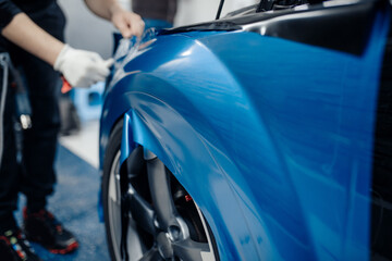 Fototapeta Car wrapping specialist putting vinyl foil or film on car. Selective focus. obraz